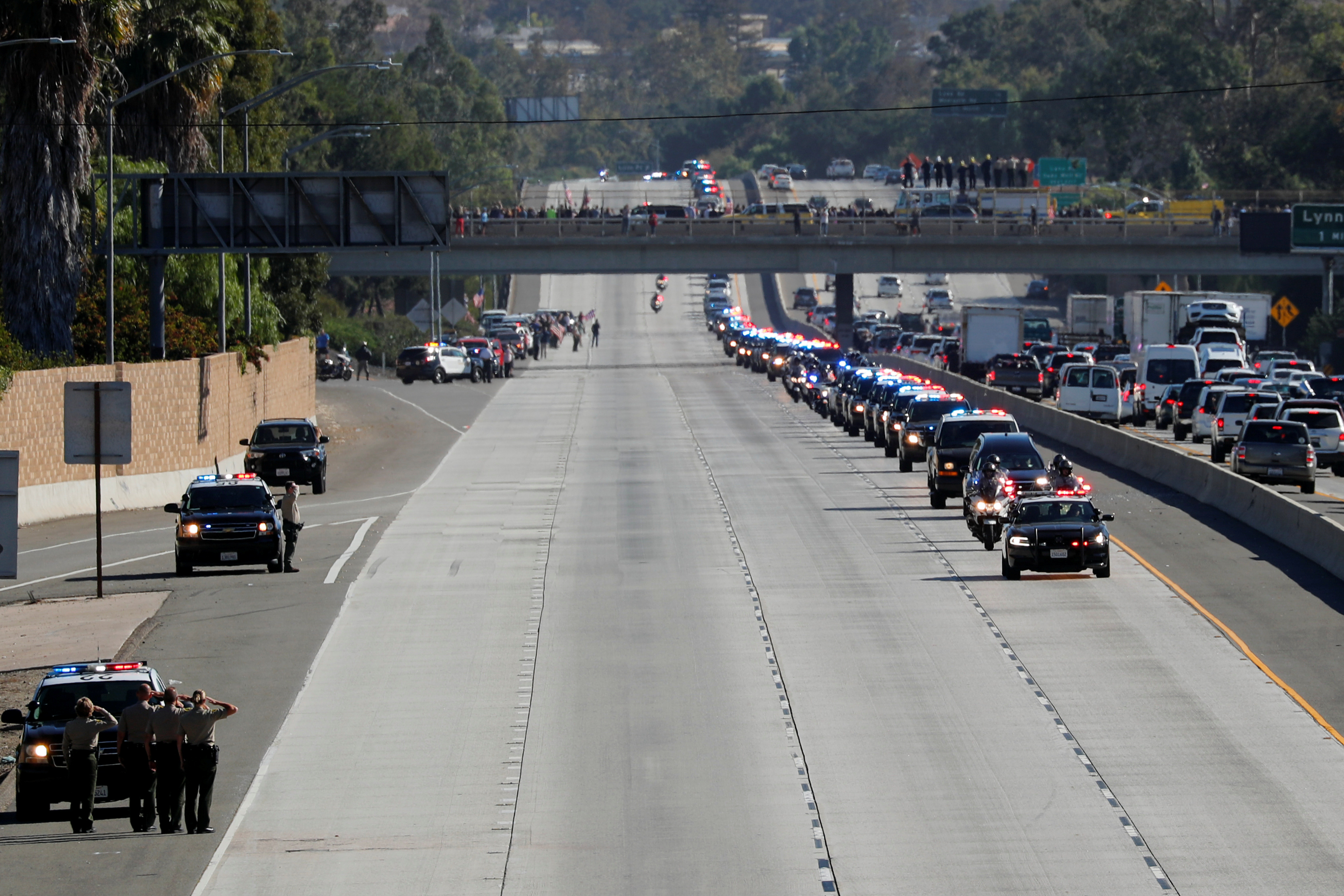 A procession for the body of Sergeant Ron Helus, who died in a shooting incident at a Thousand Oaks bar, drives down Ventura HIghway 101 in Thousand Oaks, California