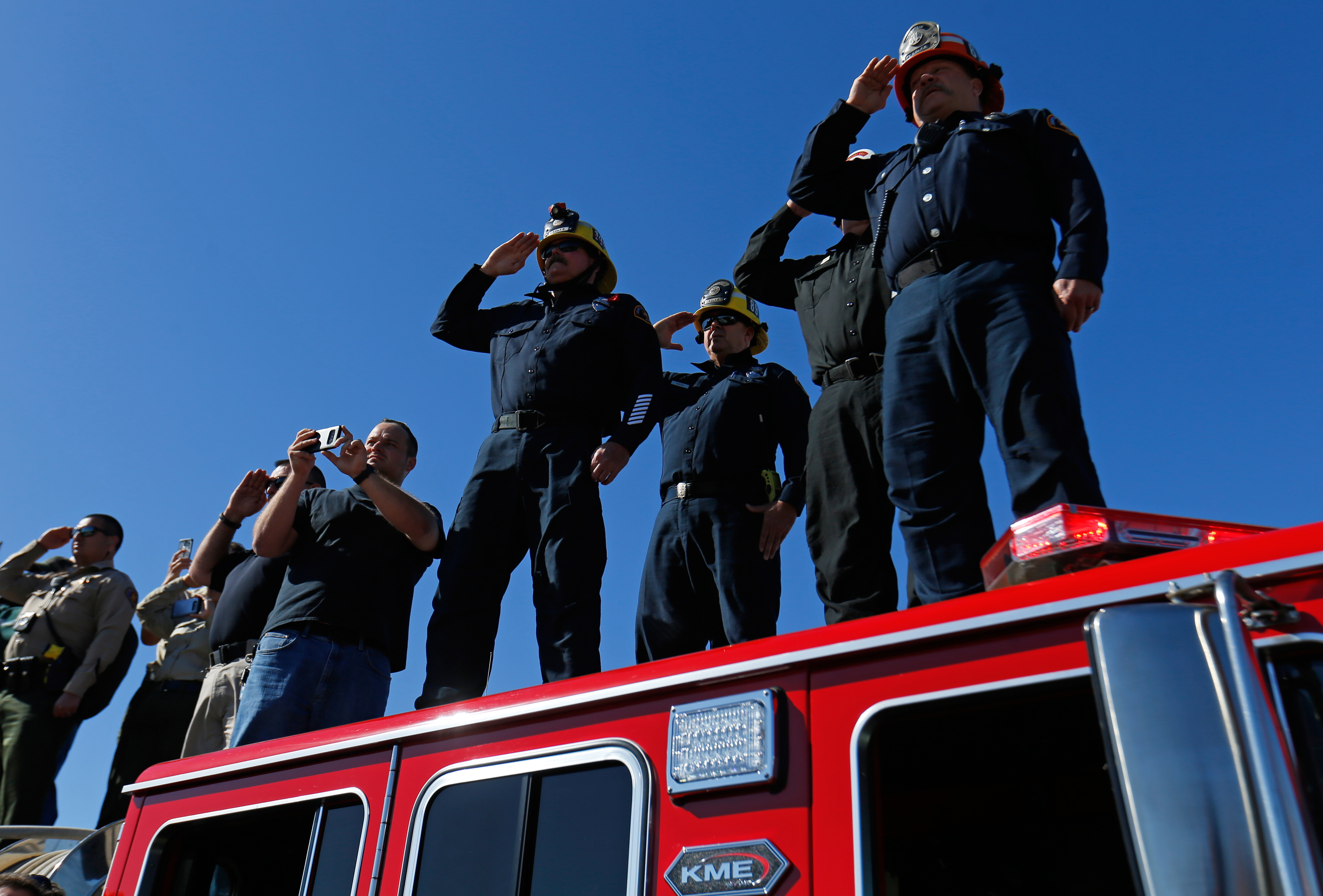 Los Angeles County firefighters salute from an overpass as a procession for the body of Sergeant Ron Helus, who died in a shooting incident at a Thousand Oaks bar, drives down Ventura HIghway 101 in Thousand Oaks