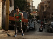 A man wearing a sleeveless shirt with the Superman logo walks along a street in Beirut, Lebanon