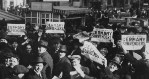 A crowd in Times Square hold up copies of newspapers with a headline about the signing of the Armistice