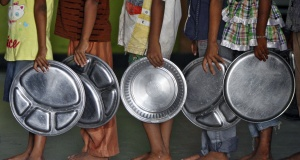 Children holding plates wait in a queue to receive food at an orphanage in the southern Indian city of Chennai