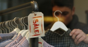 A man looks at clothes on a Sale rail inside a shop during the Christmas sales in London