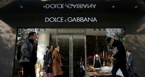 People walk past a Dolce & Gabbana store at a shopping complex in Shanghai