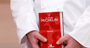 A chef holds a Michelin Guide 2018 during the Michelin Guide 2018 award ceremony at the Seine Musicale center in Boulogne-Billancourt near Paris
