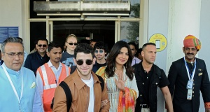 Bollywood actress Priyanka Chopra and singer Nick Jonas wave as they arrive at the airport in Jodhpur