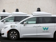 Three of the fleet of 600 Waymo Chrysler Pacifica Hybrid self-driving vehicles are parked and diaplayed during a demonstration in Chandler, Arizona