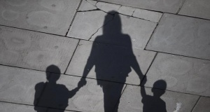 A woman and children cast their shadows as they stroll in the sunshine on the Southbank in London