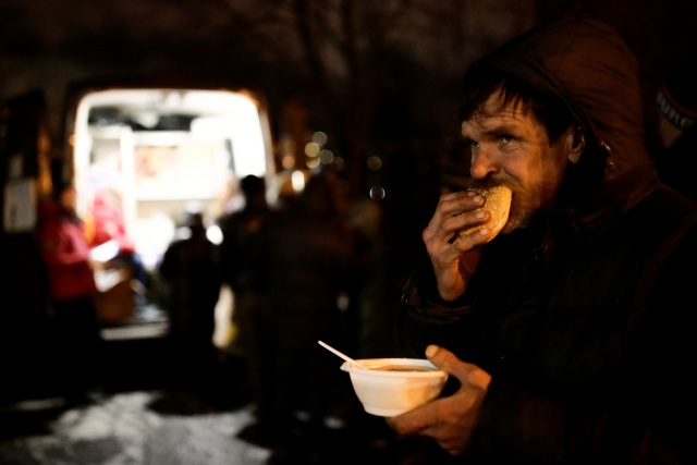 A man eats soup and bread as volunteers distribute charity meals for homeless people in St. Petersburg