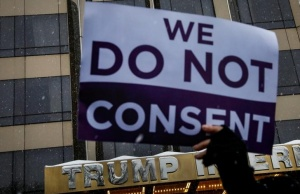 A protester holds a sign up during a #MeToo demonstration outside Trump International hotel in New York