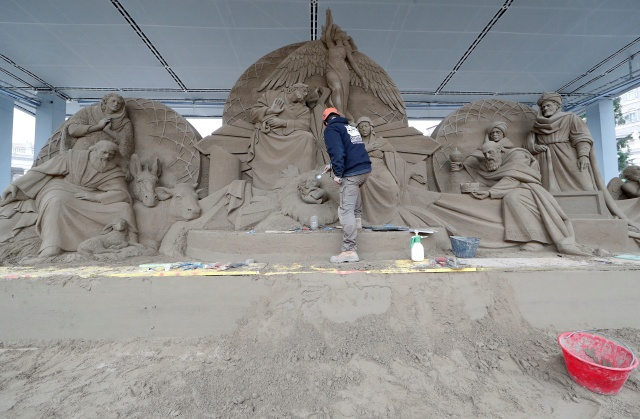 An artist works on a sand sculpture representing part of nativity scene in St. Peter's square at the Vatican