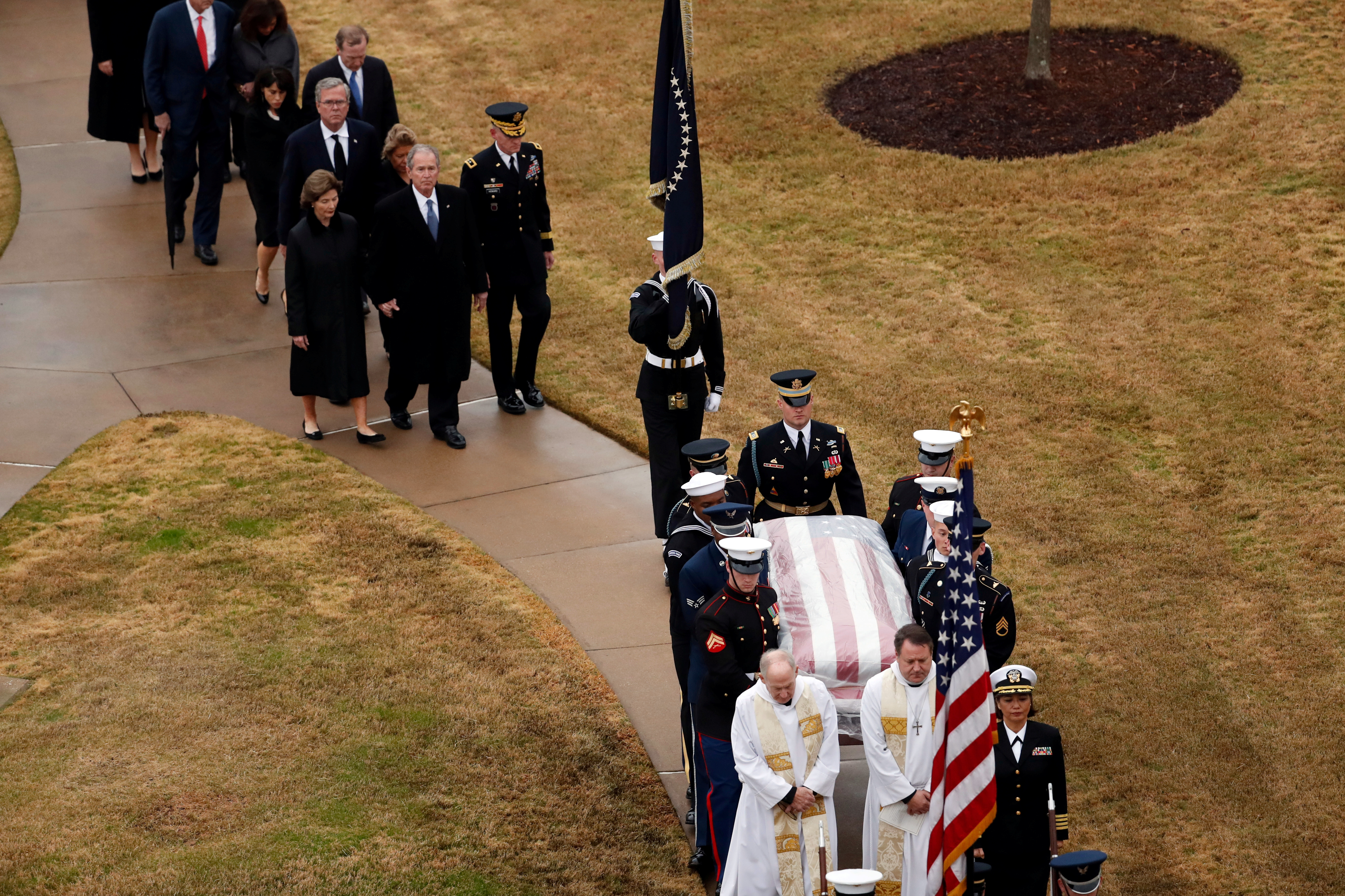 The flag-draped casket of former President George H.W. Bush is carried by a joint services military honor guard followed by family members at the George H.W. Bush Presidential Library and Museum