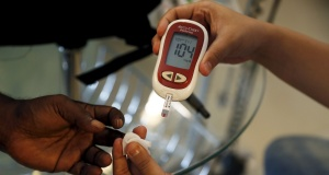 A paramedic checks the blood sugar level of a patient at SS Diabetes Care clinic in Jakarta