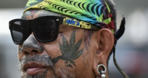 A Thai activist with a marijuana tattoo on his face gathers with others during a campaign for the legalisation of medical marijuana near Government House in Bangkok