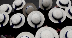 Pupils wearing boater hats as part of their school uniform pose for a group picture