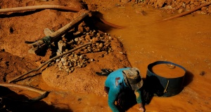A wildcat gold miner, or garimpeiro, uses a basin and mercury to pan for gold at a wildcat gold mine, also known as a garimpo, at a deforested area of the Amazon rainforest near Crepurizao, in the municipality of Itaituba