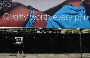 A woman walks past a Marks and Spencer's billboard advertisement in south London
